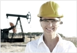 Female oil worker with helmet in front of a horsehead pump