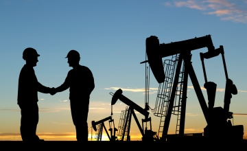 Silhouettes of 2 workers against horsehead oil pumps