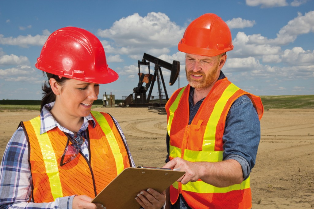 A royalty free image from the oil and gas industry of a male and female oil engineer in conversation in front of a pumpjack.